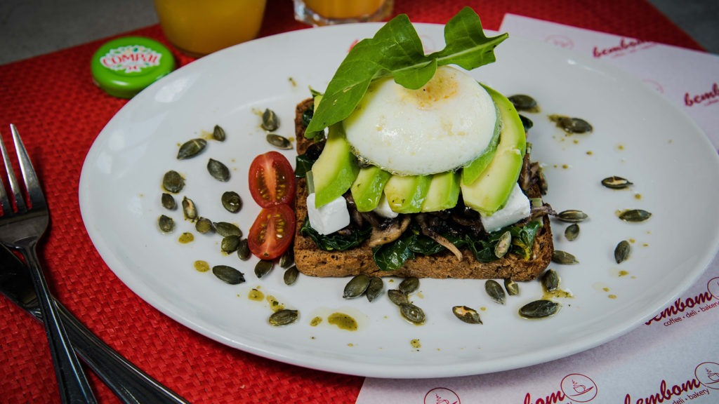 Torre Saudável – Toasted seeded bread, sautéed spinach, grilled mushrooms, avo, pumpkin seeds, basil feta & a poached egg.
