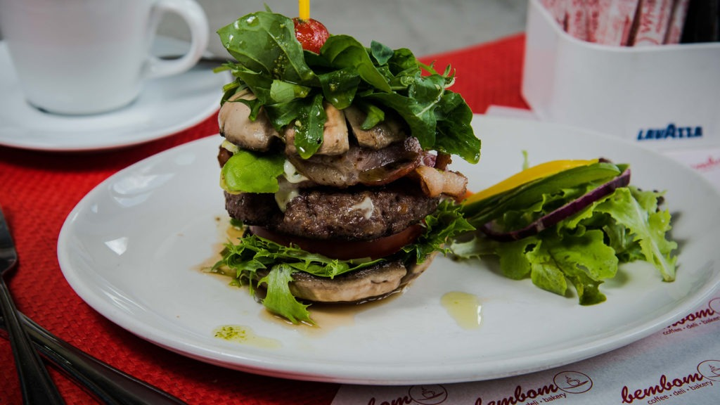 Naked Bun-less Burger – Grilled Big Brown Mushrooms, lettuce, fresh tomato, basil mayo, beef burger, avo, bacon, rocket & pesto.